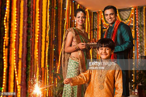 Boy burning fire crackers with his parents in the background on Diwali