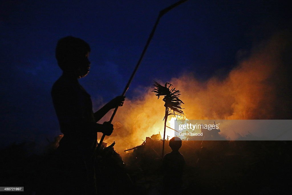 A boy burns wood on a fire near the Tacloban astrodome evactuatuion centre on November 20, 2013 in Leyte, Philippines. Typhoon Haiyan which ripped through Philippines over a week ago has been described as one of the most powerful typhoons ever to hit land, leaving thousands dead and hundreds of thousands homeless. Countries all over the world have pledged relief aid to help support those affected by the typhoon however damage to the airport and roads have made moving the aid into the most affected areas very difficult. With dead bodies left out in the open air and very limited food, water and shelter, health concerns are growing.