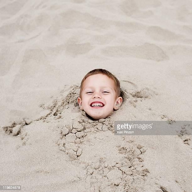 Boy (3-5) burried in sand.