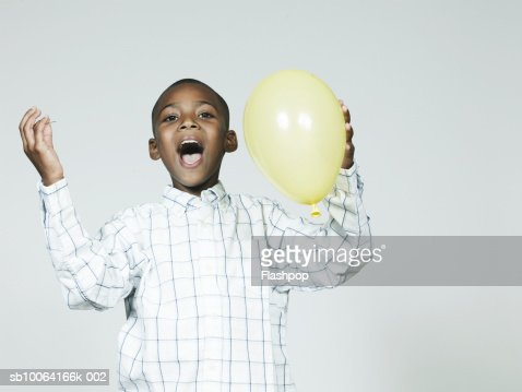 Boy (6-7) bursting balloon, laughing : Stock Photo