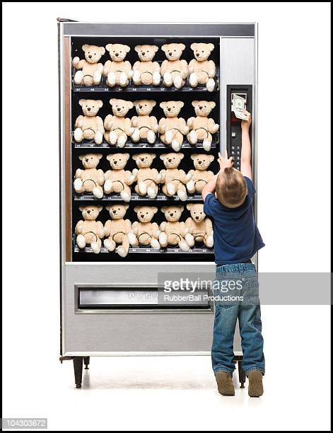 boy buying a teddy bear from a vending machine