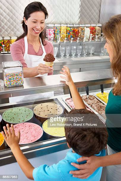 Boy buying an ice cream in ice cream parlor