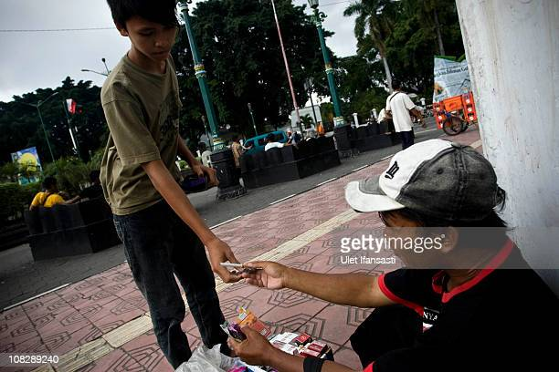 A boy buys a cigarette from a vendor on January 24 2011 in Yogyakarta Indonesia It is estimated that over 25 percent of children in Indonesia over...