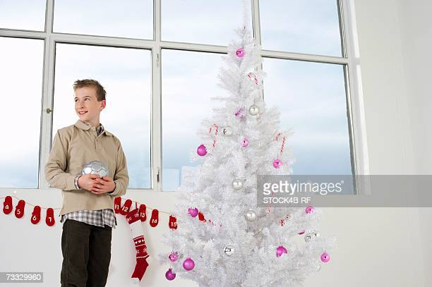 Boy by a white Christmas tree