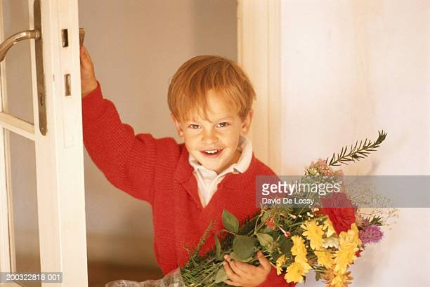 Boy (6-7) by door holding bouquet, smiling, elevated view