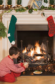 Boy by fireplace at Christmas