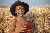 Boy (8-9) by haystack holding water bottle, smiling