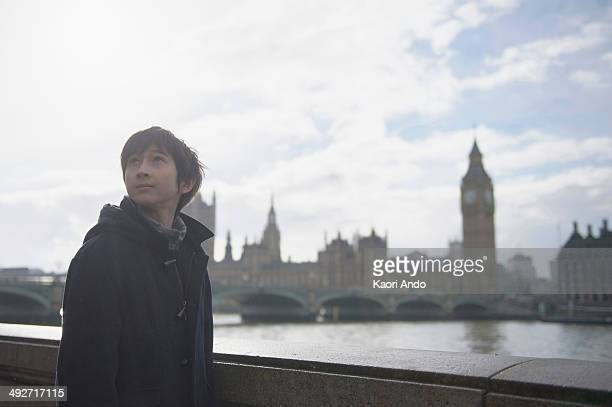 Boy by River Thames, Palace of Westminster in background, London