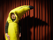 Boy (5-7) by stage curtain wearing banana costume, portrait, close-up