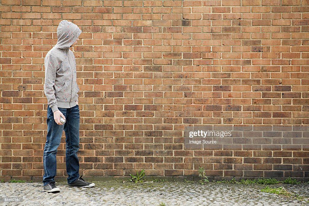 Boy by wall with spray can