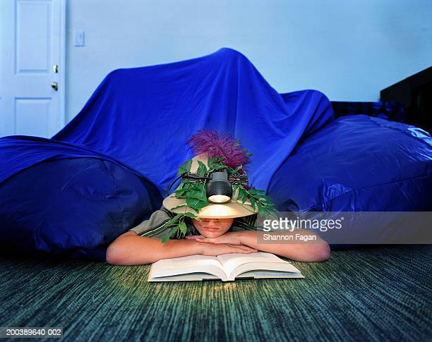 Boy ((11-13) camping indoors, wearing pith helmet, reading book