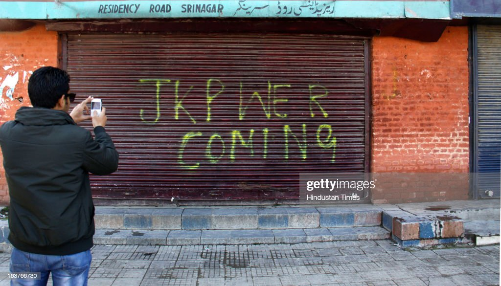 A boy captures on his camera the writing on the shutter during a curfew on March 15, 2013 on Srinagar, India. Curfew continued for the second consecutive day in Srinagar district following the alleged firing by CRPF personnel on Wednesday in which a youth was killed. CRPF personnel allegedly opened fire after coming under attack by a group of stone pelters while on their way to hospital to donate blood for their colleagues injured in terror attack.
