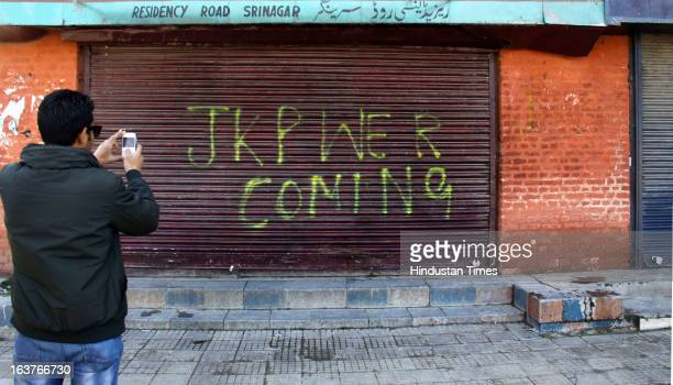 A boy captures on his camera the writing on the shutter during a curfew on March 15 2013 on Srinagar India Curfew continued for the second...