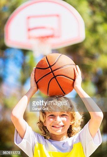 Boy (8-9) caring basketball on head
