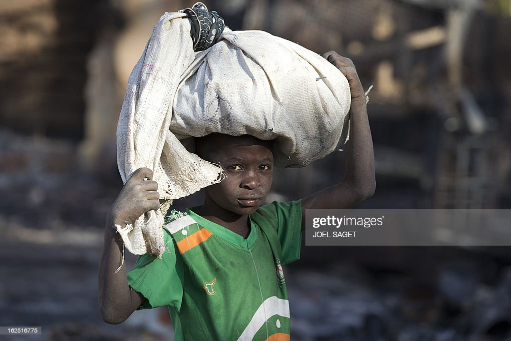 A boy carries a bag as he searches for goods on February 24, 2013 in Gao's market which allegedly burnt down following an attack by Islamist militants on February 21, 2013 in Gao, some 1,200 kilometres (745 miles) north of Bamako. Fresh fighting erupted yesterday in northern Mali between ethnic Tuaregs and an unidentified armed group, security sources told AFP, the latest violence in the wake of a French-led campaign that drove radical Islamist fighters from major cities. AFP PHOTO /JOEL SAGET