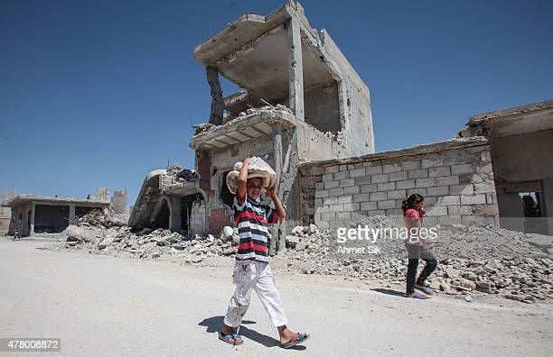 A boy carries bread as he walks past the destroyed buildings in the Syrian town of Kobane also known as Ain alArab Syria June 20 2015 Kurdish...