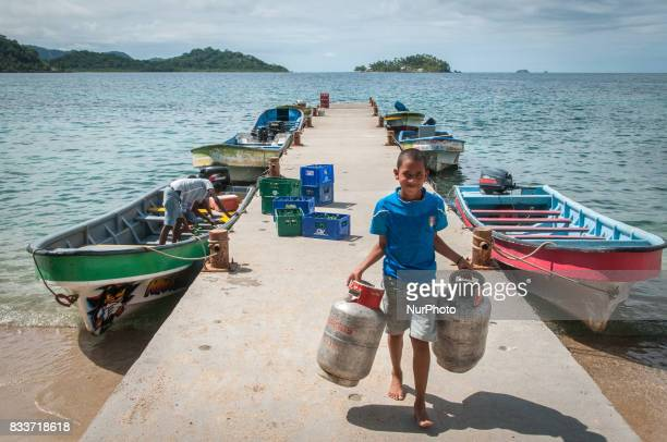 A boy carries gas canisters on a boat dock in Nombre de Dios Panama on 9 December 2011