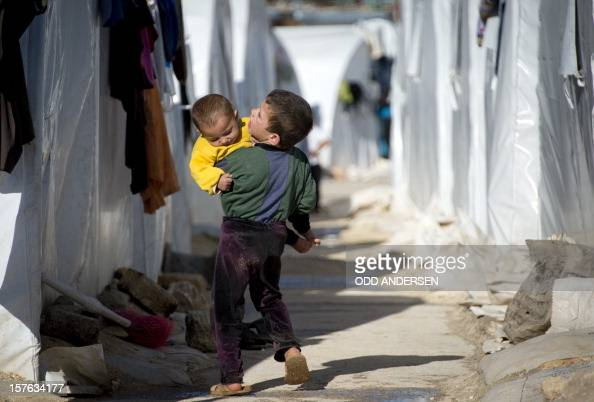 A boy carries his younger brother back to their tent in a refugee camp on the border between Syria and Turkey near the northern city of Azaz on...