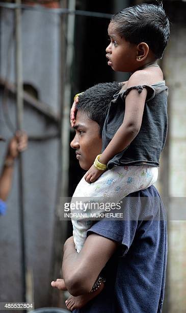 A boy carries his younger sibling on his shoulder as he watches a traditional Lavani folk dance performance for sex workers in the red light district...