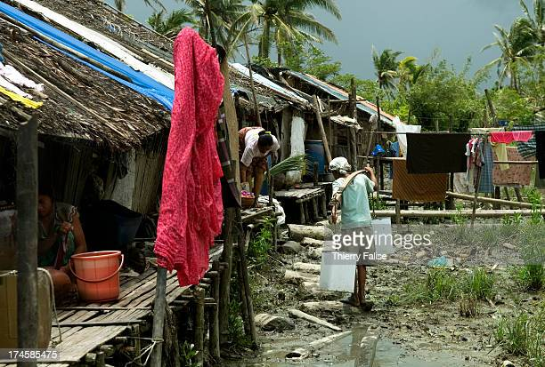 A boy carries water in a village devastated by cyclone Nargis Houses have been rebuilt with palm leaves and tarpaulin According to official figures...