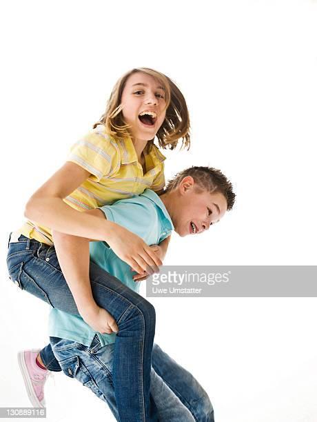 A boy carrying a girl piggyback
