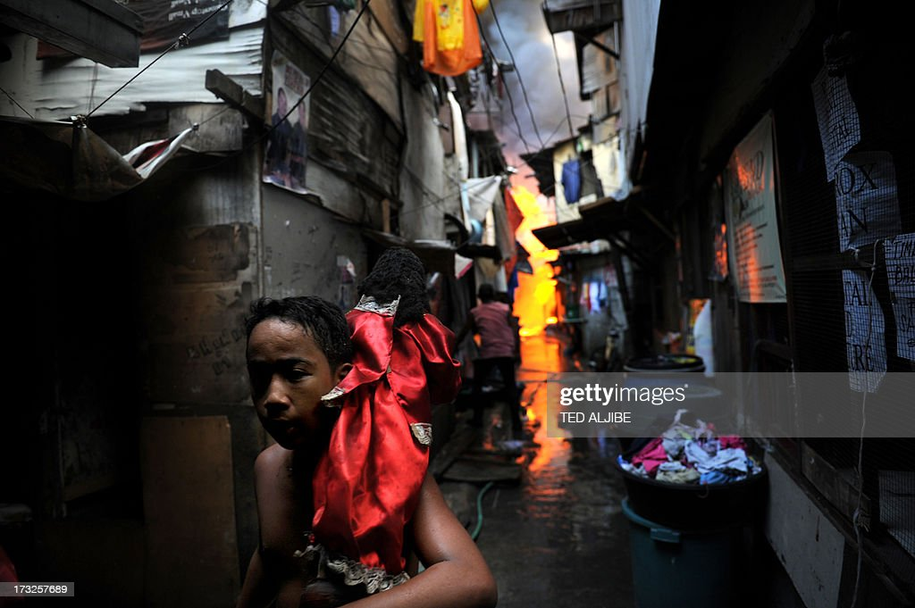 A boy carrying a religious statue runs from burning houses after a fire engulfed a shanty town at the financial district of Manila on July 11, 2013. There were no immediate reports of casualties from the blaze, which occurred mid-morning amid government plans to relocate thousands of families living in areas vulnerable to floods and typhoons.