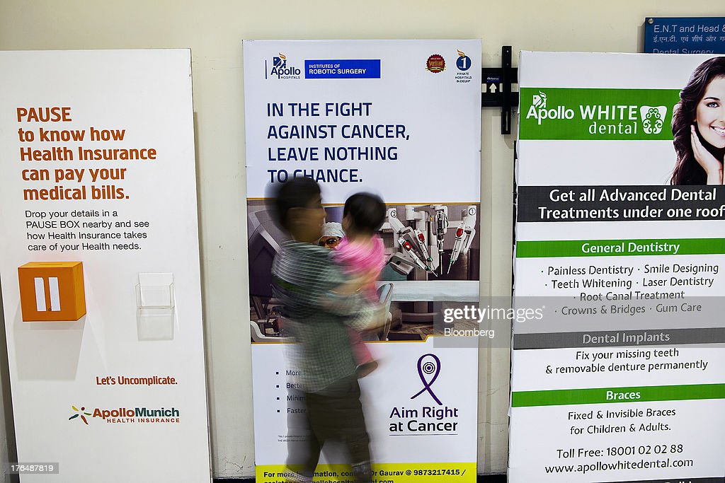 A boy carrying a small child walks past advertisements for health care services outside the Wellness Center of the Indraprastha Apollo Hospitals facility, operated by Apollo Hospitals Enterprise Ltd., in New Delhi, India, on Wednesday, July 19, 2013. Prathap C. Reddy, the cardiologist who built the Apollo hospital chain valued at $2 billion over three decades in India, says hes seeking growth overseas as the nations visa policies drive medical tourists to rivals. Photographer: Prashanth Vishwanathan/Bloomberg via Getty Images