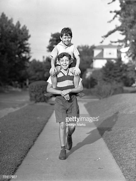 Boy (10-11) carrying brother (6-7) on shoulders, (B&W), portrait