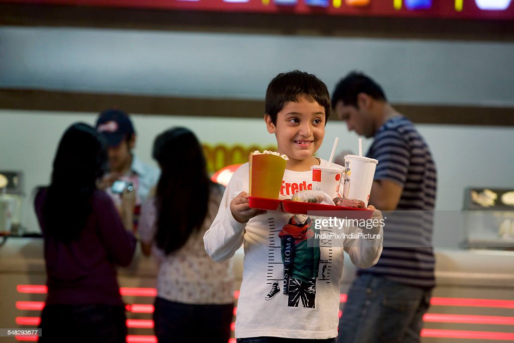 Boy carrying cola and popcorn : Stock-Foto