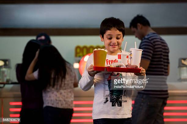 Boy carrying cola and popcorn