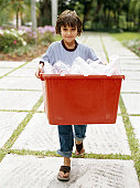 Boy (5-7) carrying crate of empty plastic bottles for recycling