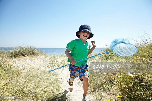 Boy carrying fishing net on beach