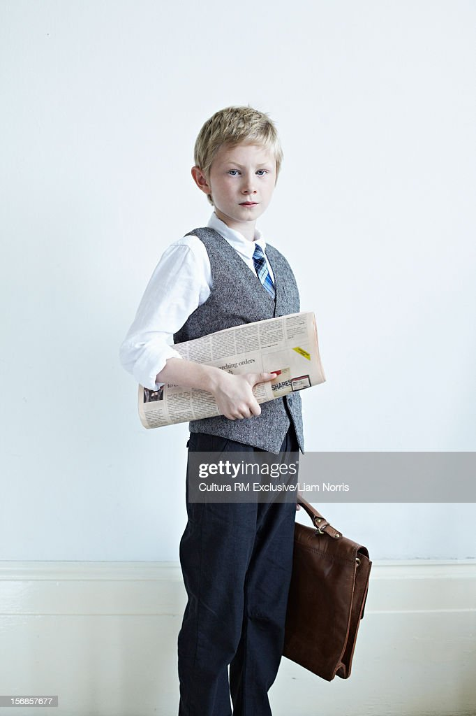 Boy carrying newspaper and briefcase : Stock Photo