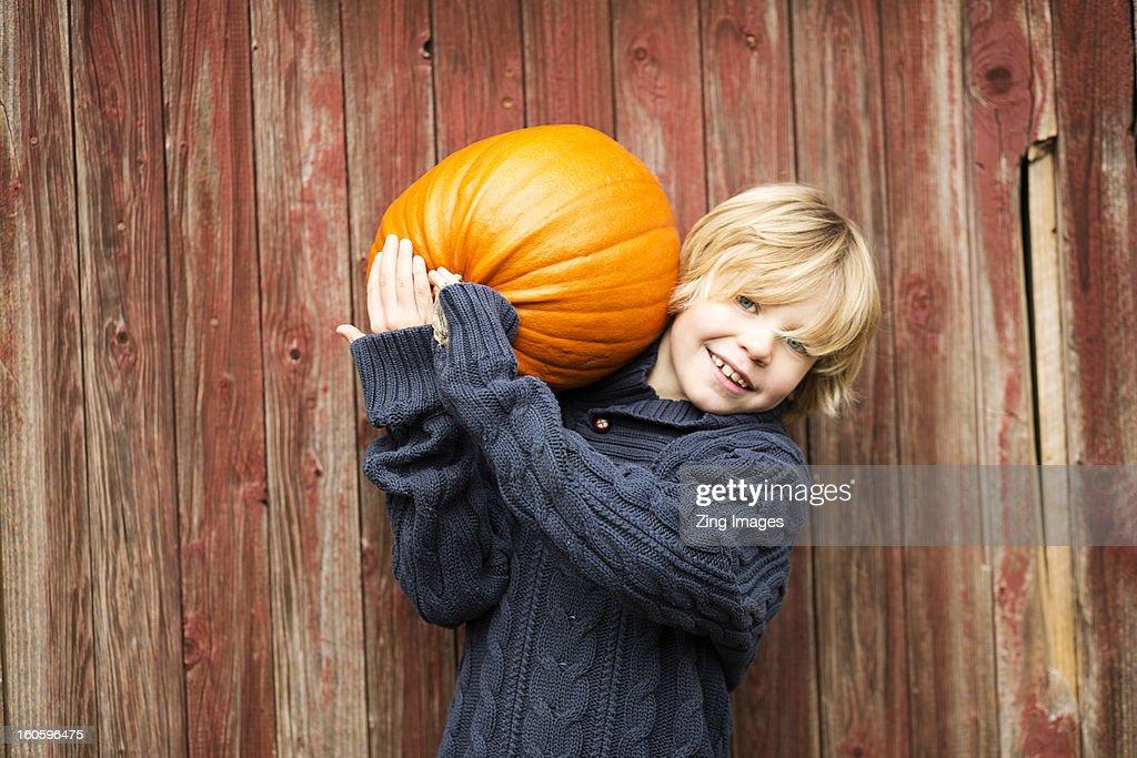 Boy carrying pumpkin : Stock Photo