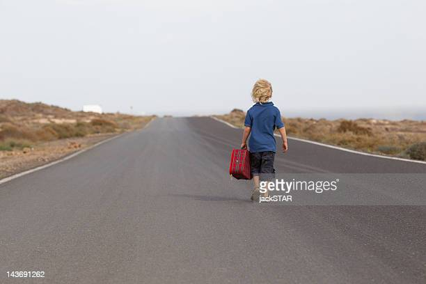 Boy carrying suitcase on rural road