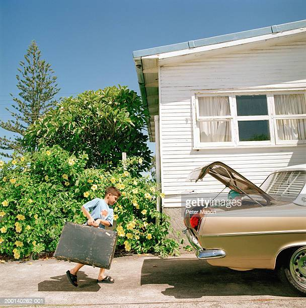 Boy (6-8) carrying suitcase to car