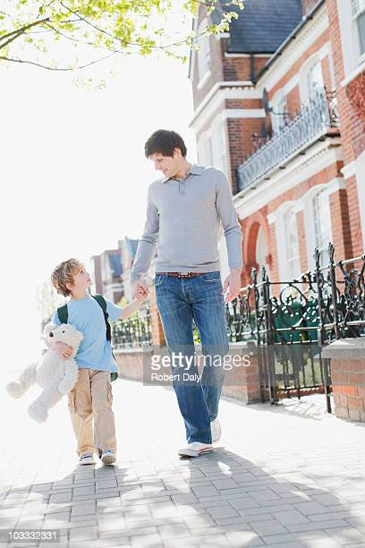 Boy carrying teddy bear and holding fathers hand on sidewalk