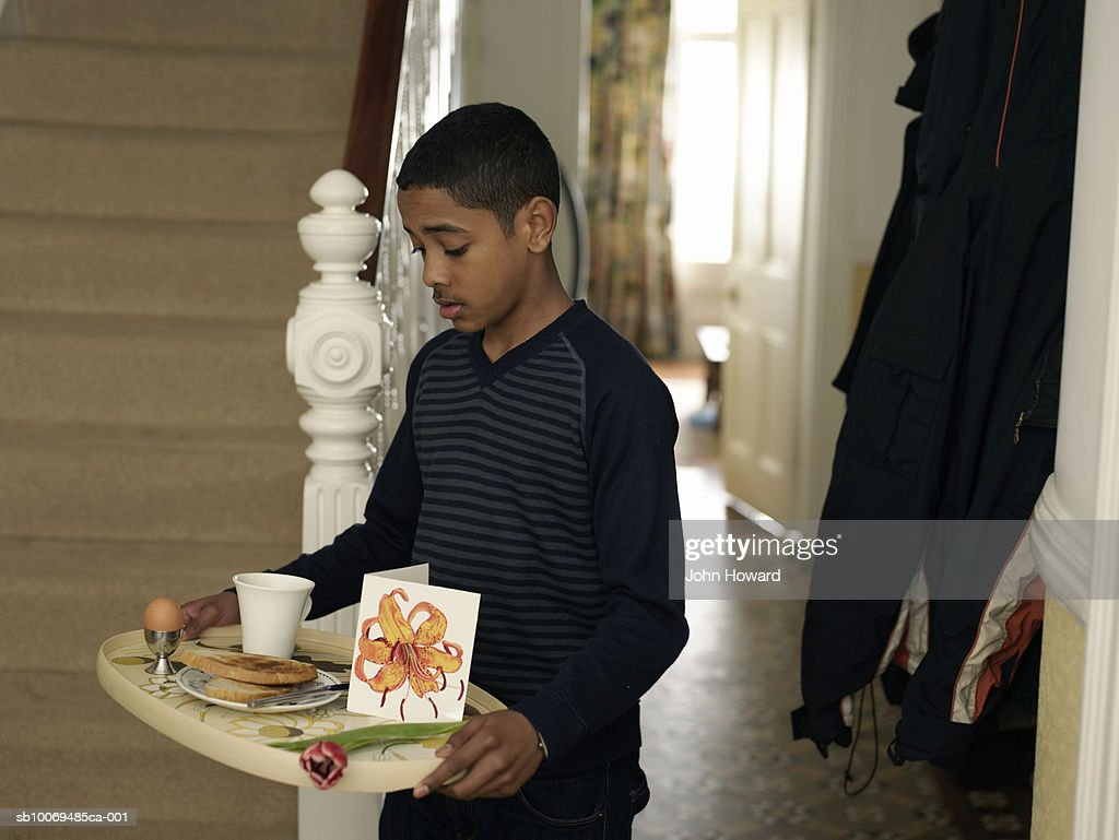 Boy (12-13) carrying tray with breakfast and flower through hallway : Stock Photo