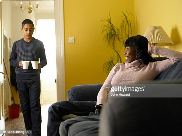 Boy (12-13) carrying two mugs, mother sitting on sofa
