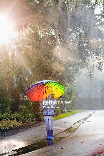 Boy carrying umbrella and looking up on street