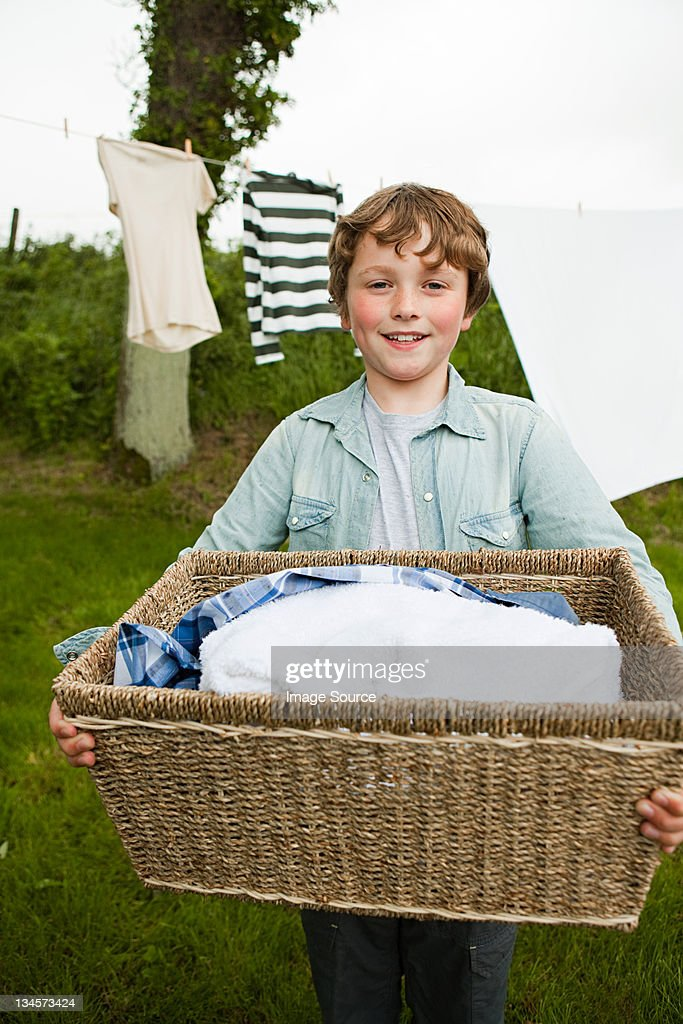 Boy carrying washing basket : Stock Photo
