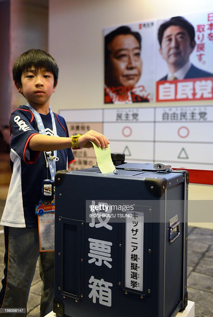 A boy casts a mock vote in a straw poll for the upcoming general election at the Kidzania career theme park in Tokyo on December 14, 2012. A group of elementary schoolchildren visiting the theme park took part in the exercise in the hope of teaching young people about the country's election process. Japan's young people in their 20s, alienated and outnumbered by a greying population, will barely bother to vote in weekend polls after a campaign that excluded social media and made little effort to engage them. Ruling Democratic Party of Japan leader and prime minister, Yoshihiko Noda (C), and opposition Liberal Democratic Party (LDP) leader Shinzo Abe are pictured in the background. AFP PHOTO / Yoshikazu TSUNO