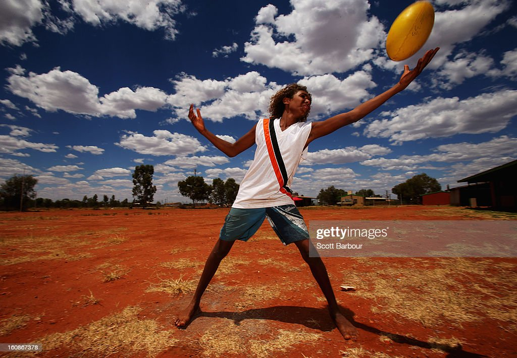 A boy catches an Australian rules football as members of the Indigenous All Stars visit Yuendumu School in the Australian outback ahead of the AFL exhibition match between the Richmond Tigers and the Indigenous All Stars on February 7, 2013 in Yuendumu, Australia.