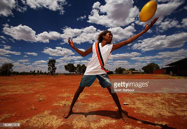 A boy catches an Australian rules football as members of the Indigenous All Stars visit Yuendumu School in the Australian outback ahead of the AFL...