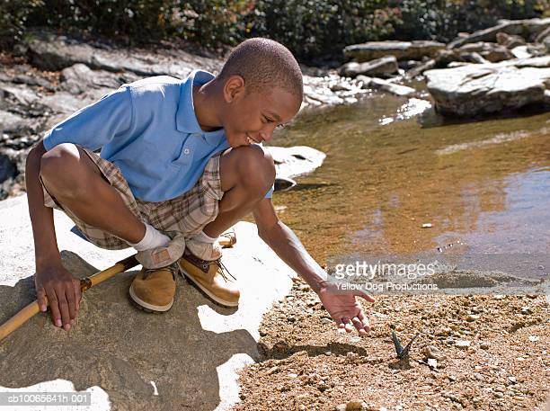 Boy (12-13) catching butterfly by stream, smiling