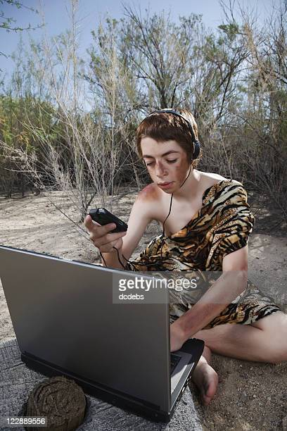 Boy Caveman Wearing Headphones with Laptop Computer and Music Player