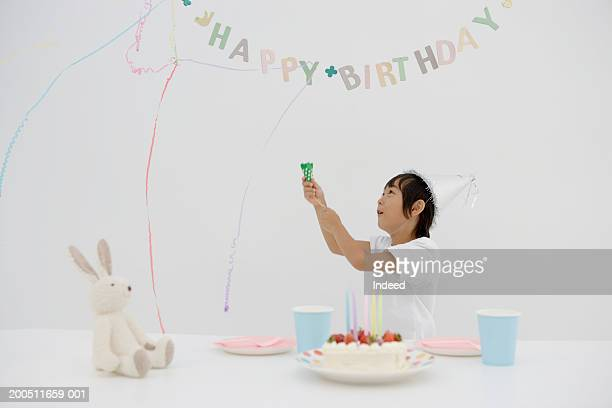 Boy (4-6) celebrating birthday, releasing party popper into air