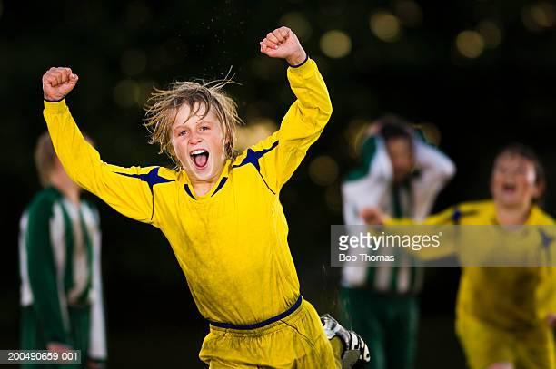 Boy (11-13) celebrating during football game, close-up