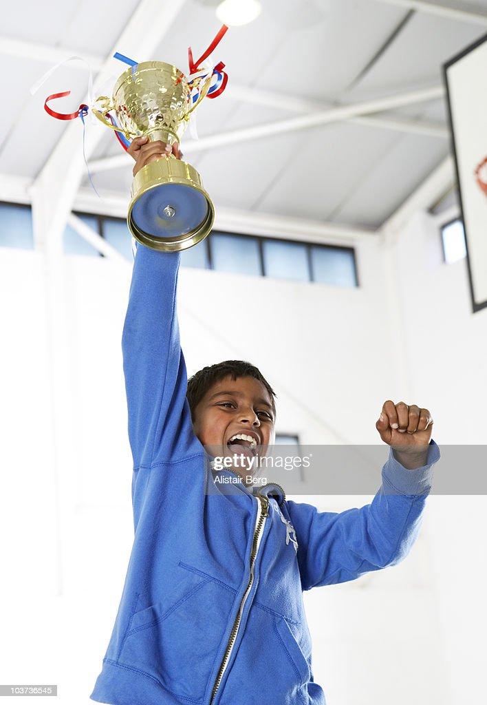 Boy celebrating in gymnasium : Stock Photo