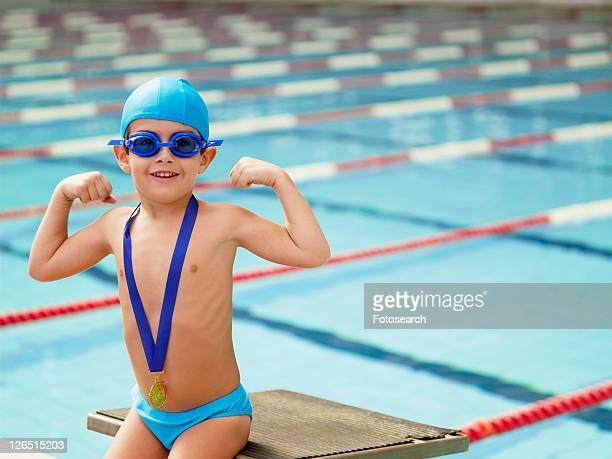 Boy celebrating medal by swimming pool (portrait)
